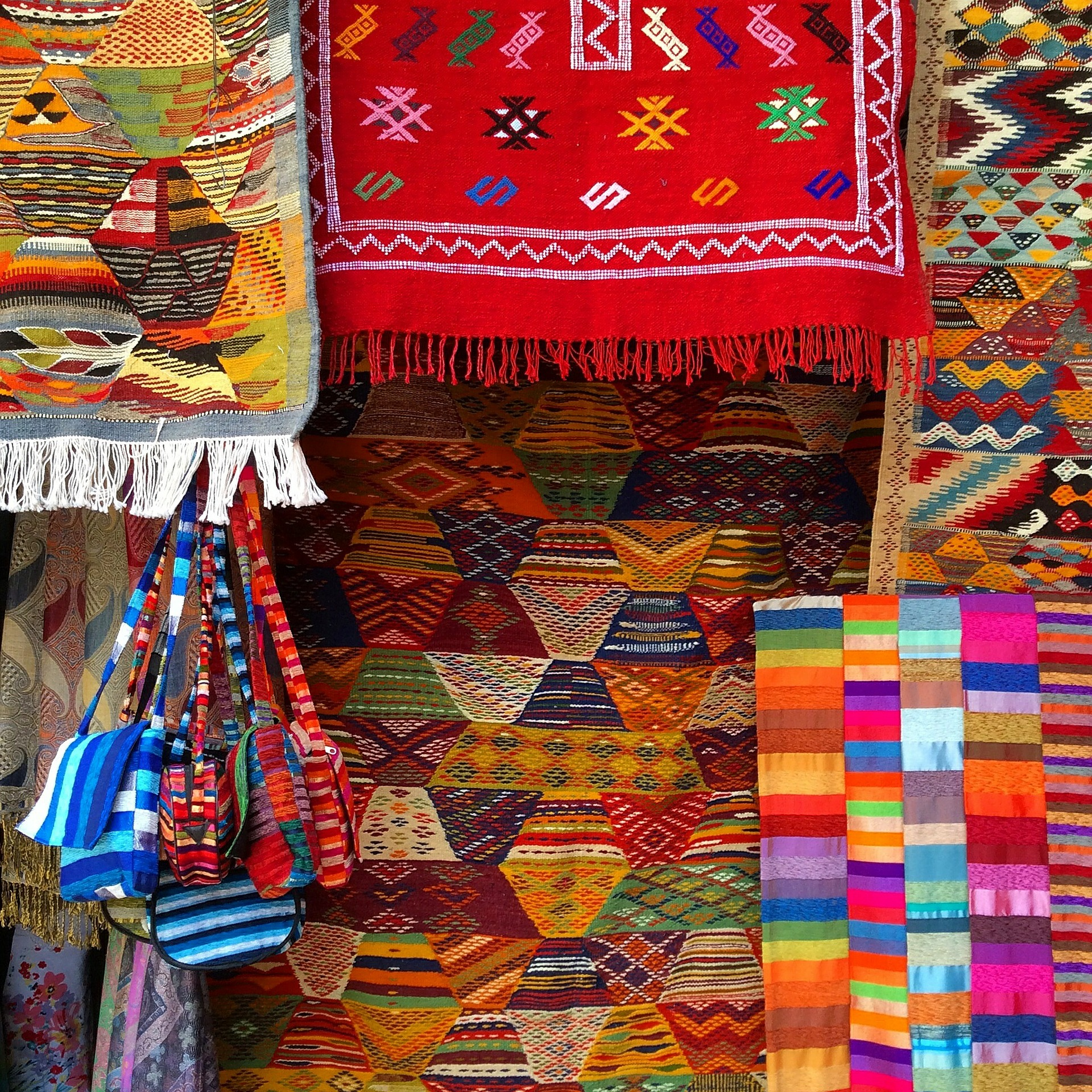 colorful Moroccan carpets hanging in front of a shop.