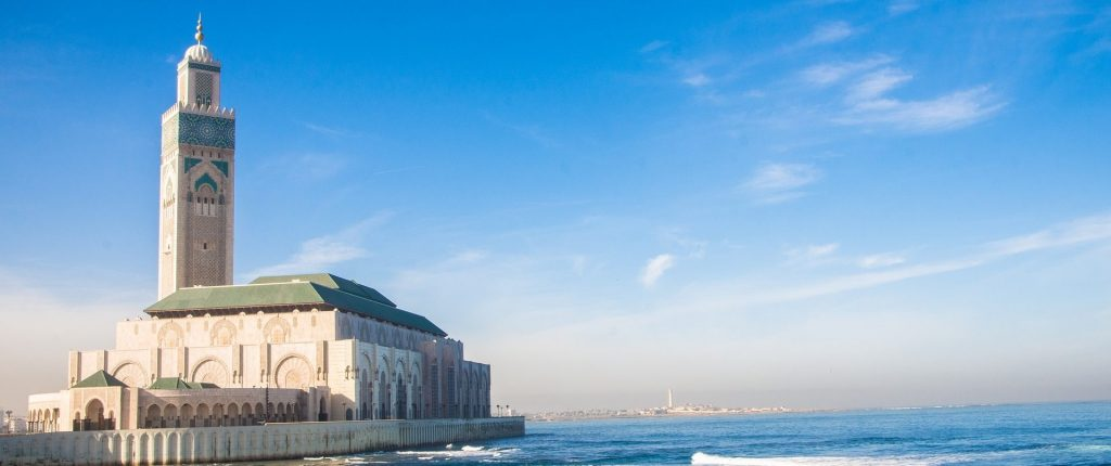 Photography of Hassan II Mosque in Casablanca as seen from a nearby walkway. The ocean is on the right.