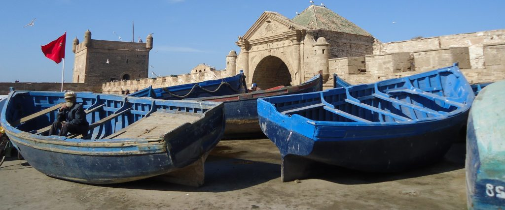 Closeup of blue row boats in front of a fortified wall in Essaouira, Morocco.