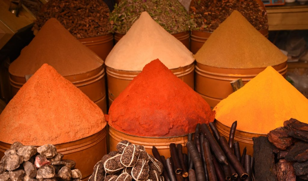 Containers of Moroccan spices on display in a market. The spices have been mounded into cones.